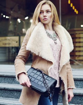 Outdoor portrait of young beautiful fashionable woman posing on street. Model wearing stylish winter fake fur coat, holding small black quilted bag. Lady looking aside. Waist up. Toned